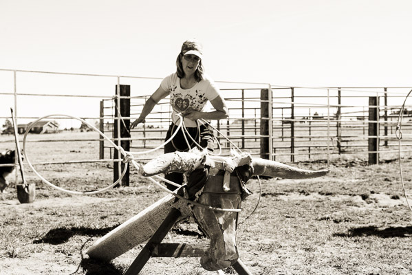 Woman roping a dummy steer.