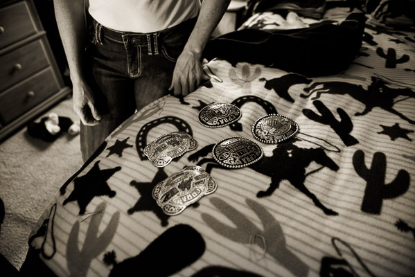 A bunch of rodeo buckles on display over a western style beadspread.