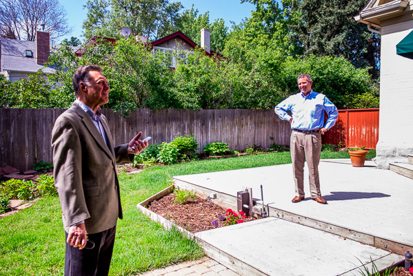 Andrew Nagel and John Sullivan talking in a yard.
