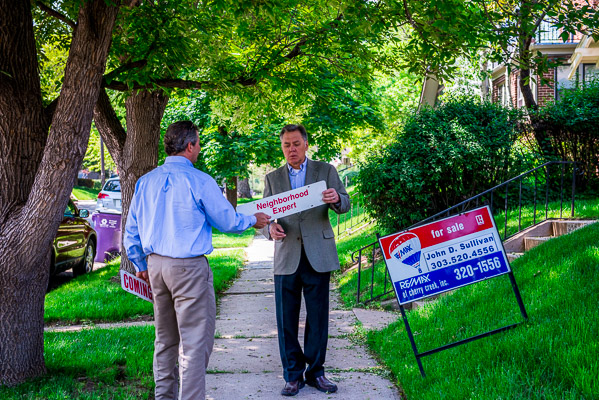 Andrew Nagel and John Sullivan put up a Neighborhood Expert sign.