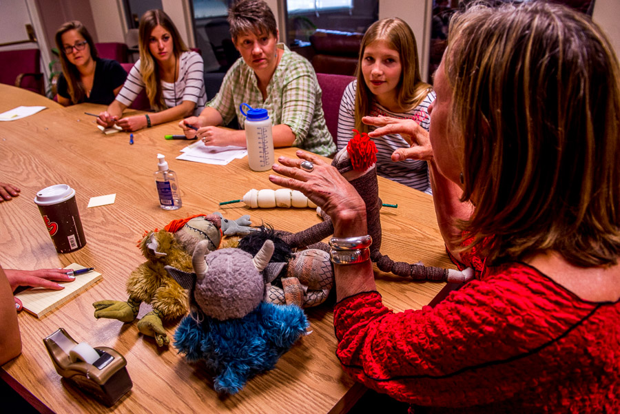 Woman using props to train staff using stuffed animals as props.