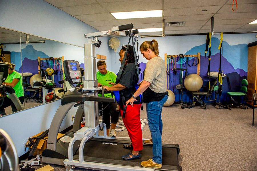 Two physical therapists help a woman using a LiteGait.