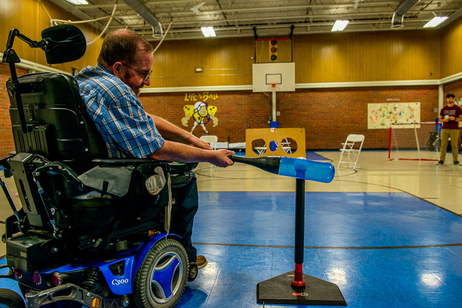 Man in a wheelchair plaing indoor softball.