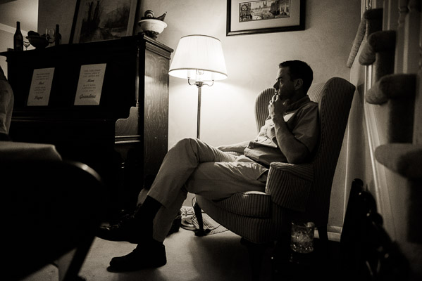 Man sitting in a chair next to a lamp.