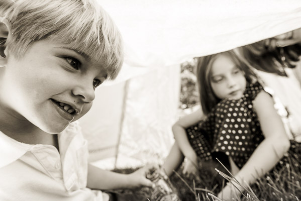 Boy and girl playing under a tent.