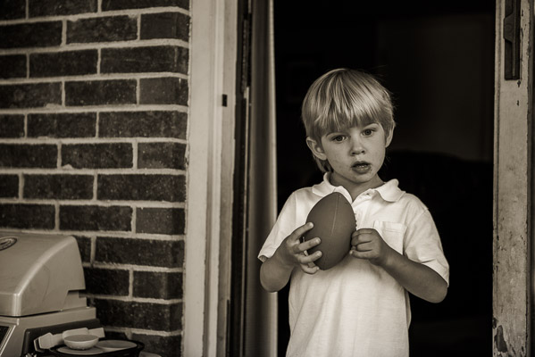 Little boy holds a football in a doorway.