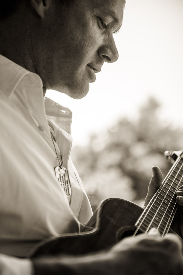Profile of handsome man playing guitar.