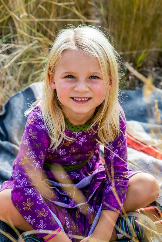 Cute little girl in purple dress in fall grass.