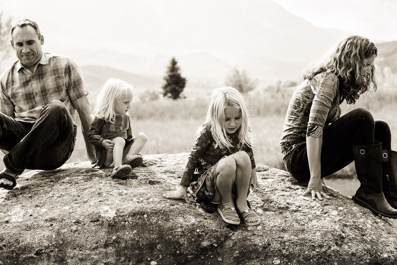 Black and white photo of a family dismounting huge rock.