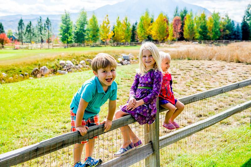 Three kids sitting on a fence.