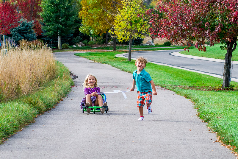 Kids playing on a path surrounded by fall trees.