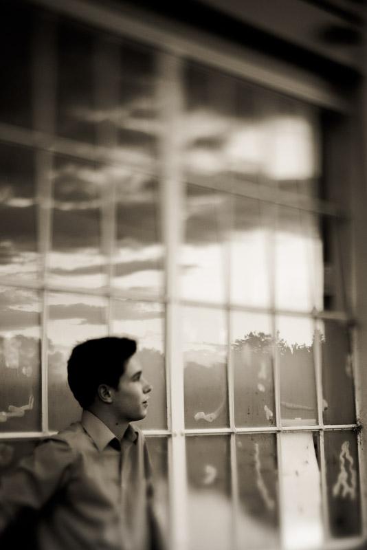 Artistic senior guy photo next to windows