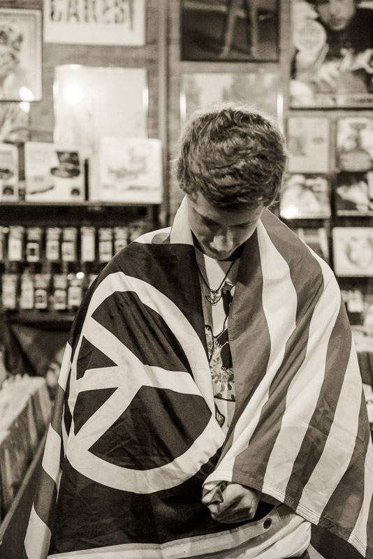 high school senior boy in record store wrapped in a peace sign flag