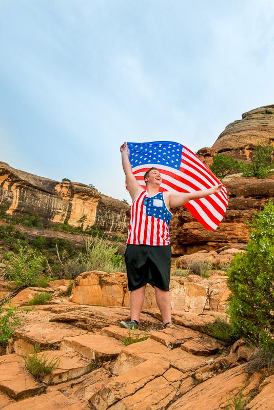 Senior boy wearing american flag shirt holding an american flag.