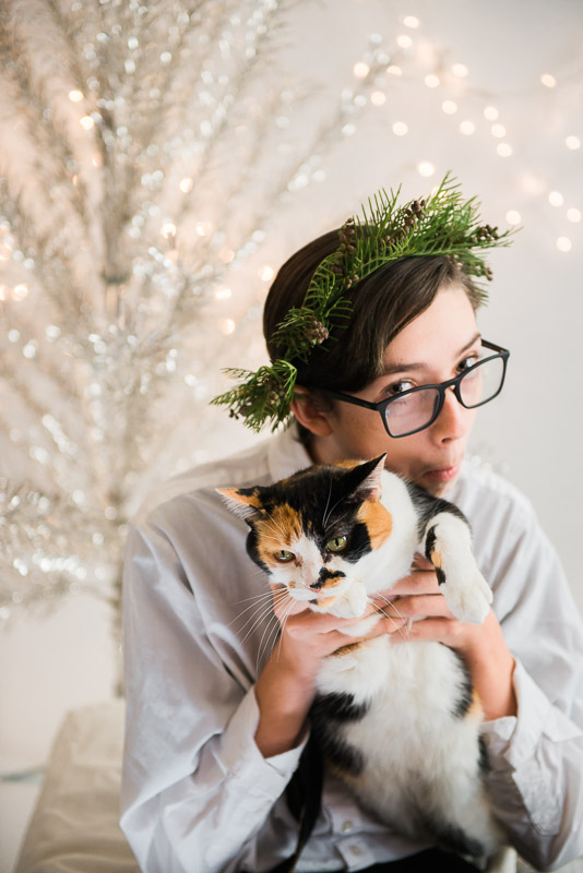 christmas theme teen boy holding a cat