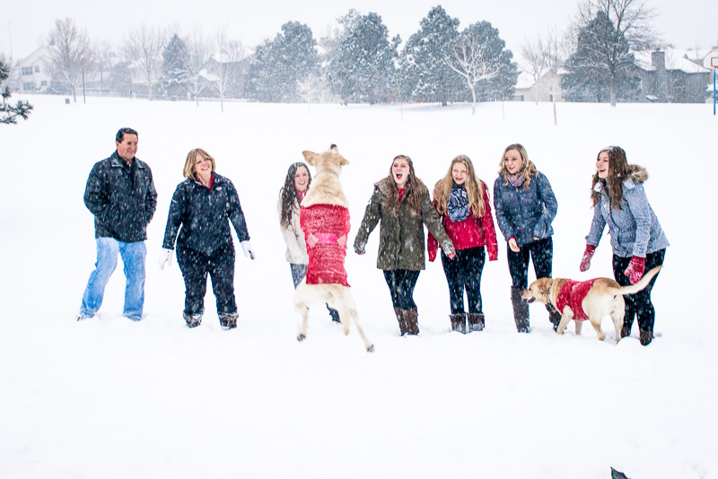 Group photo in the snow with dog photobomb.