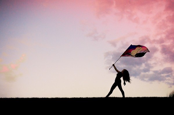 High impact senior photo of a girl holding a flag at sunset