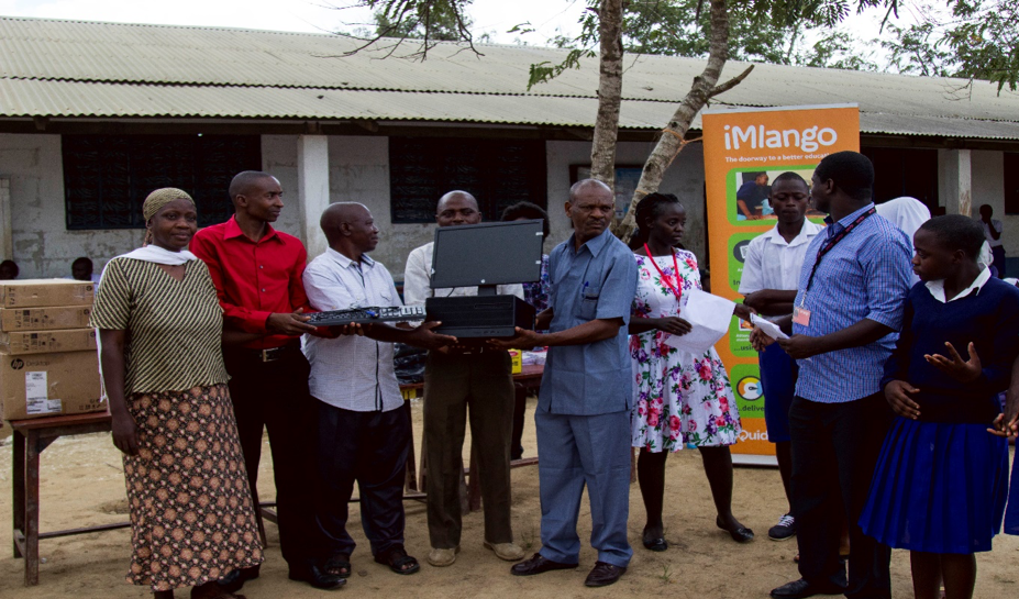 Board of Management (BoM) members of a primary school receiving ICT equipment from iMlango in a primary school in Kilifi.