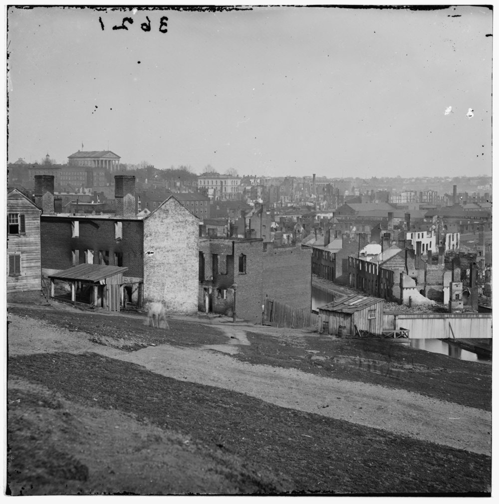This view of Richmond from Gambles Hill, just north of Tredegar Iron Works and today adjacent to the Virginia War Memorial, reveals the city's devastation following its burning by retreating Confederates.  The photo was taken by Alexander Gardner in April 1865, within weeks of the city's liberation.  The State Capitol appears at the top left.  (Library of Congress) Click the image to enlarge.
