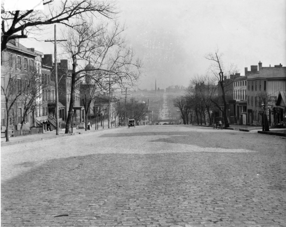 The Dabney family lived at 1414 East Broad Street in Richmond, one block east of this view, starting in 1866.  This early 20th-century image of the 1300 block nearly matches their view looking east, with Shockoe Valley below and Church Hill beyond.   (The Valentine.)
