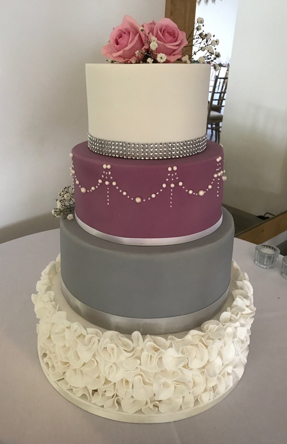 Four tier wedding cake with fondant ruffles, piped pattern and diamonte trim