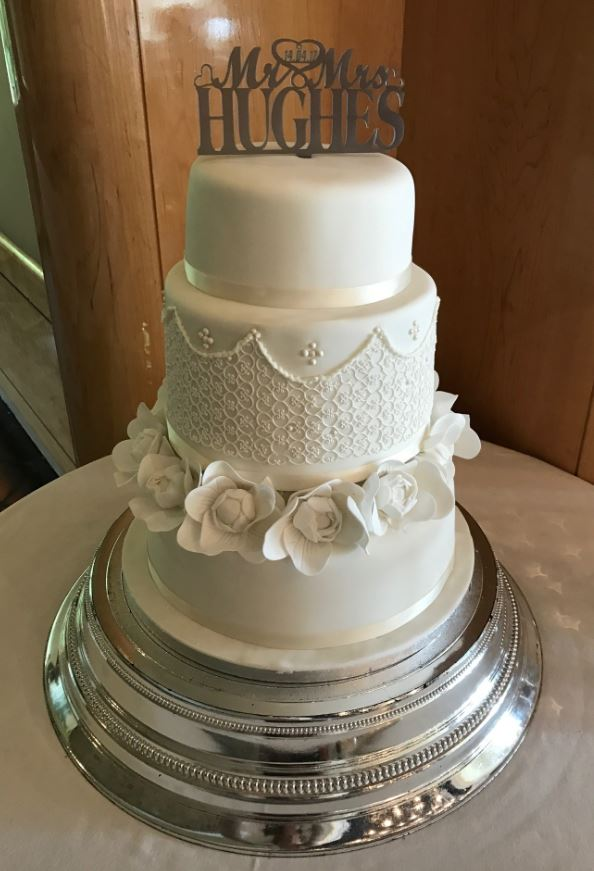 Ivory three tier wedding cake with edible lace detail and edible gardenia flowers