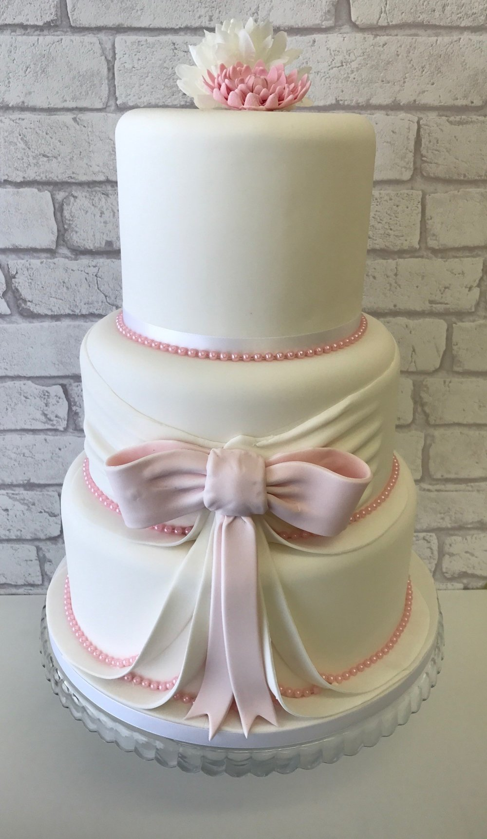 Three tier wedding cake or baby shower cake with pink fondant bow