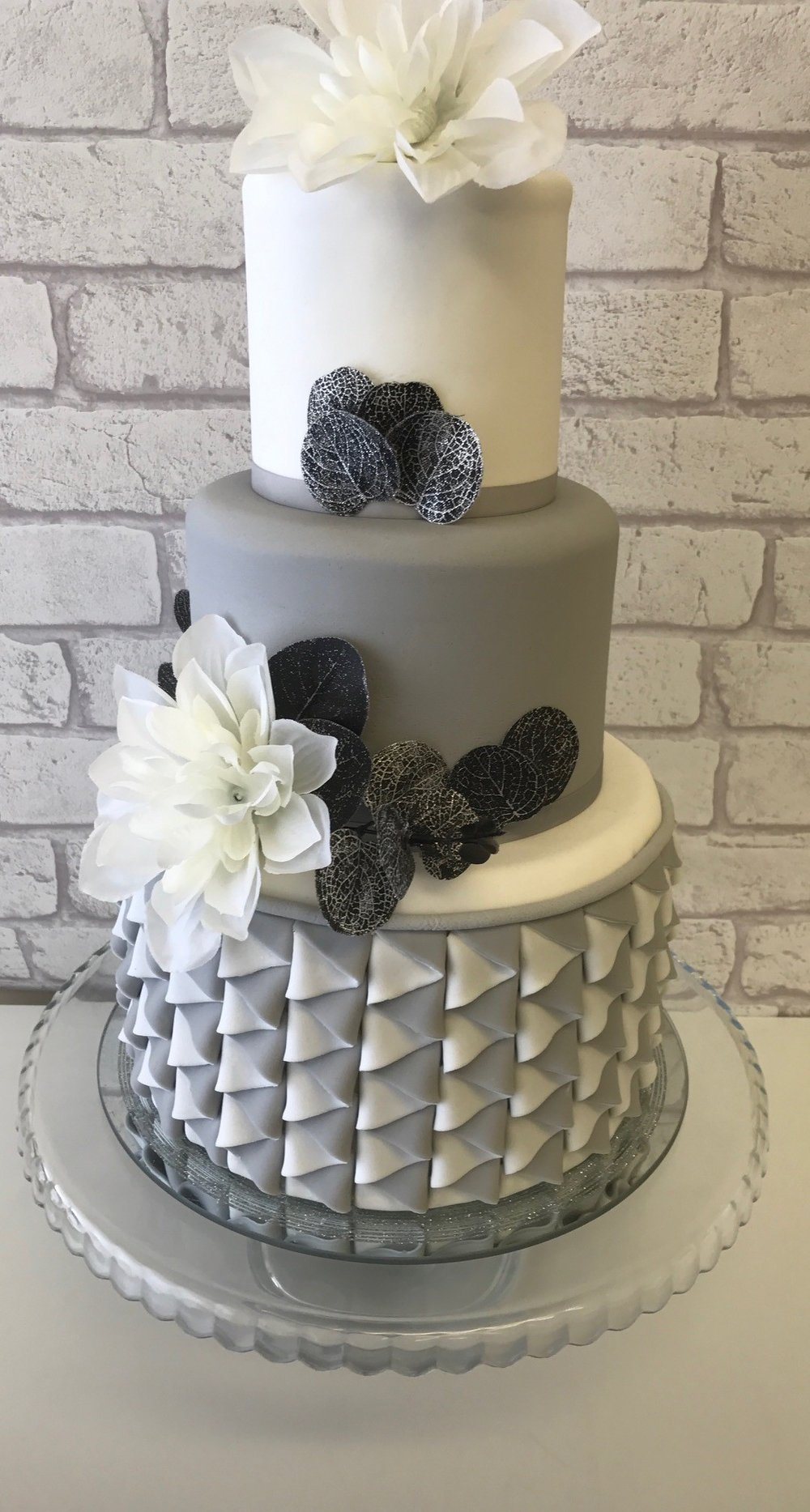 Three tier grey wedding cake with grey and white zig zag pattern on botom tier