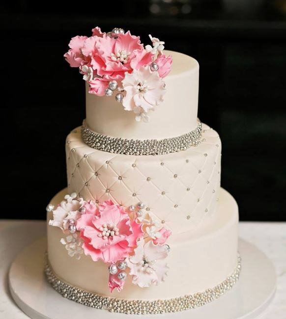 Three tier quilted wedding cake with edible white and pink peonies and a diamonte trim