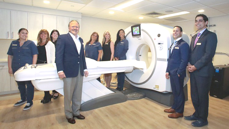 Thomas Peterffy (left front), Dr. Ben Hakim (second from right), Dr. Dan Yadegar (far right) and the staff of Holistic Integrative Health stand near what the group says is the only Cat Scan machine in Palm Beach. Yadegar described it as a state-of-the-art, low-radiation, high resolution, multi-slice GE Cat scanner. Damon Higgins / Daily News