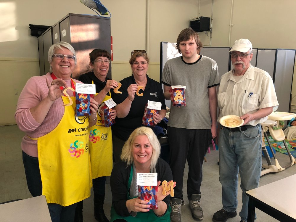 Sheila, Sue (Co-Managers), Joy Fyckes (RECLAIM), Austen (volunteer) Frank (volunteer) and kneeling, Marg Legault (Literacy Quebec)