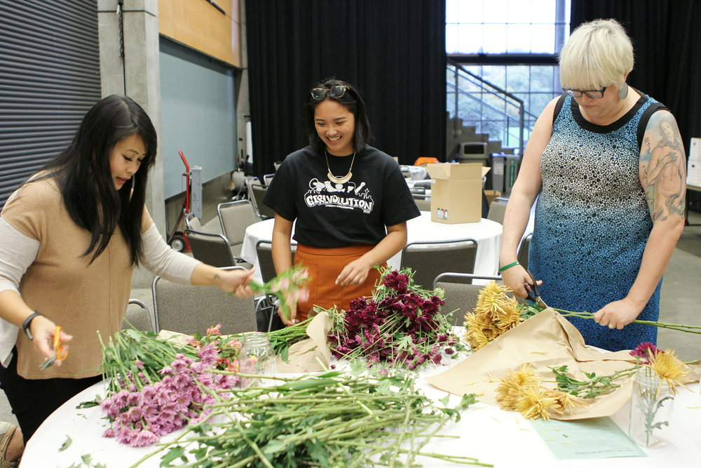 Volunteers trimming and arranging flower centerpieces at our 2017 Luncheon: SHEro POWer