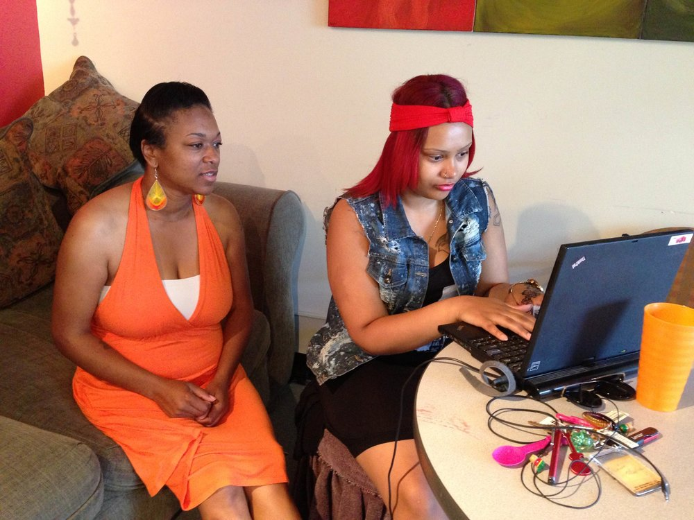 A former case manager and a young person using a laptop to do research for homework.