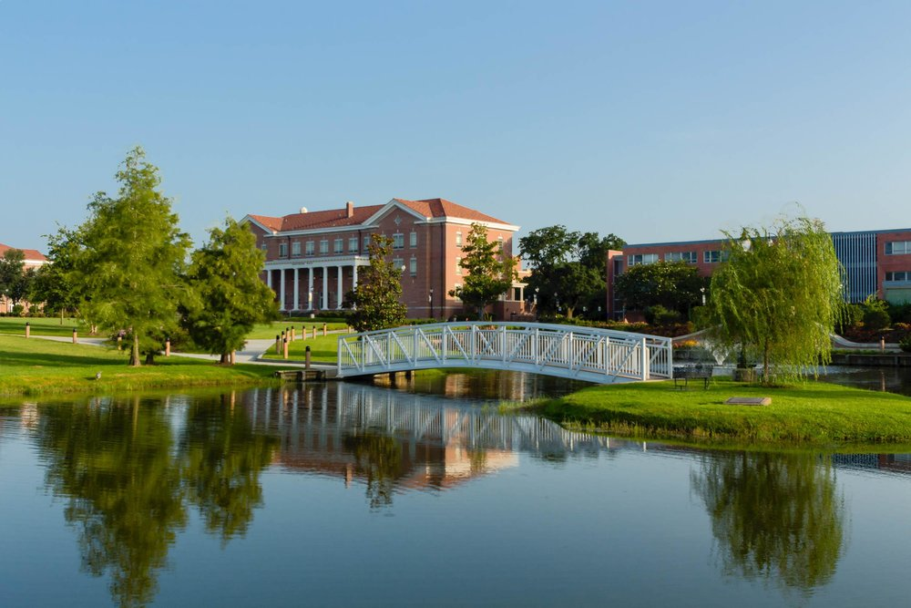 Campus buildings reflect onto Lake Byron on the campus of the University of Southern Mississippi in Hattiesburg