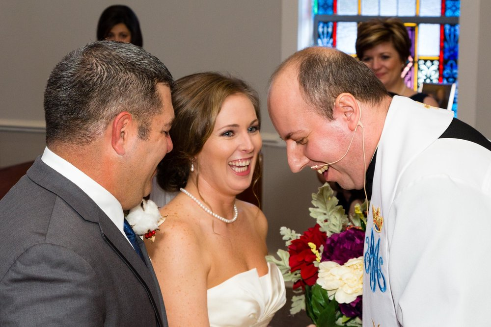 The priest tells a joke to calm the bride and groom.