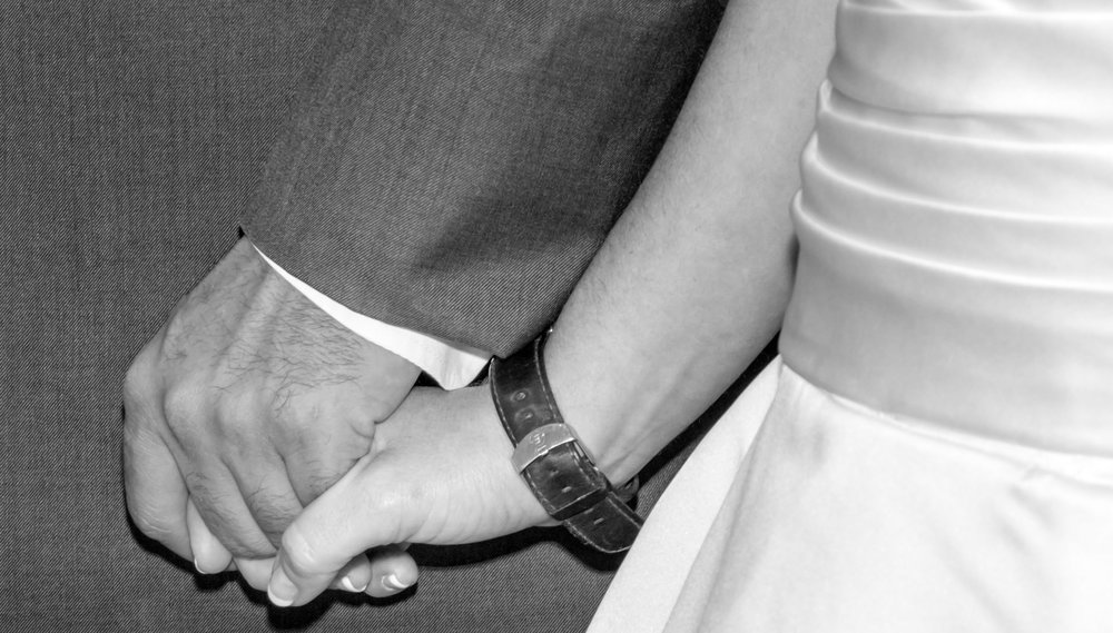 Bride and Groom hold hands.