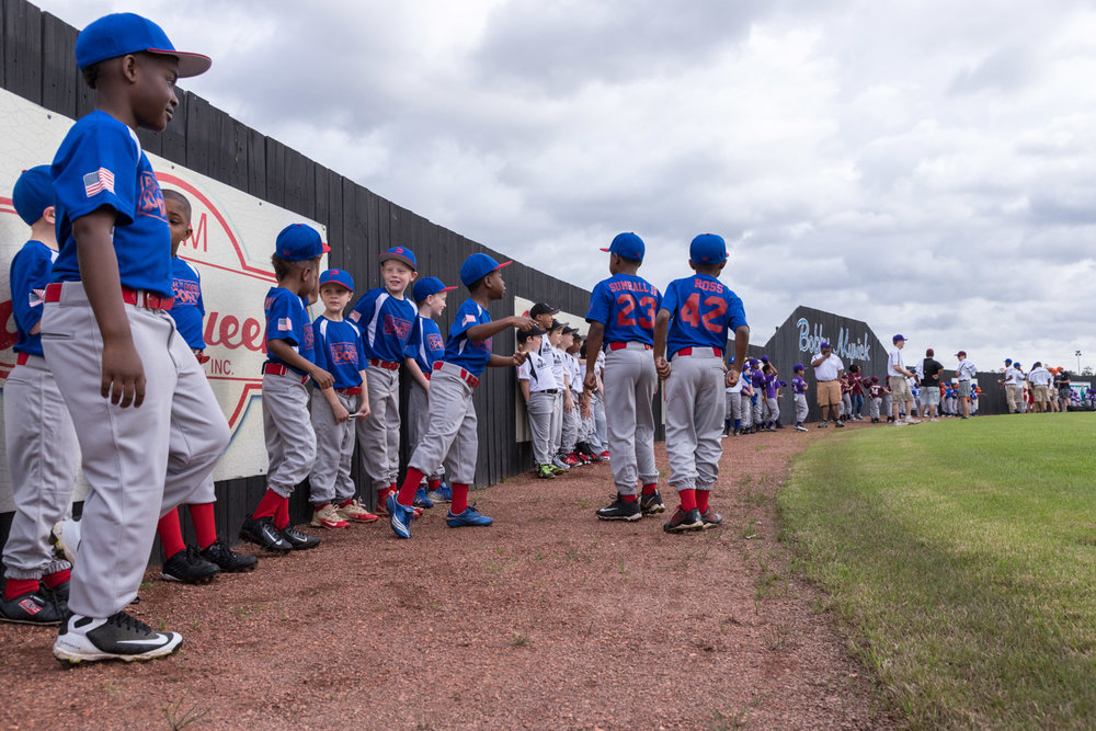 Little league baseball players line up along the outfield wall