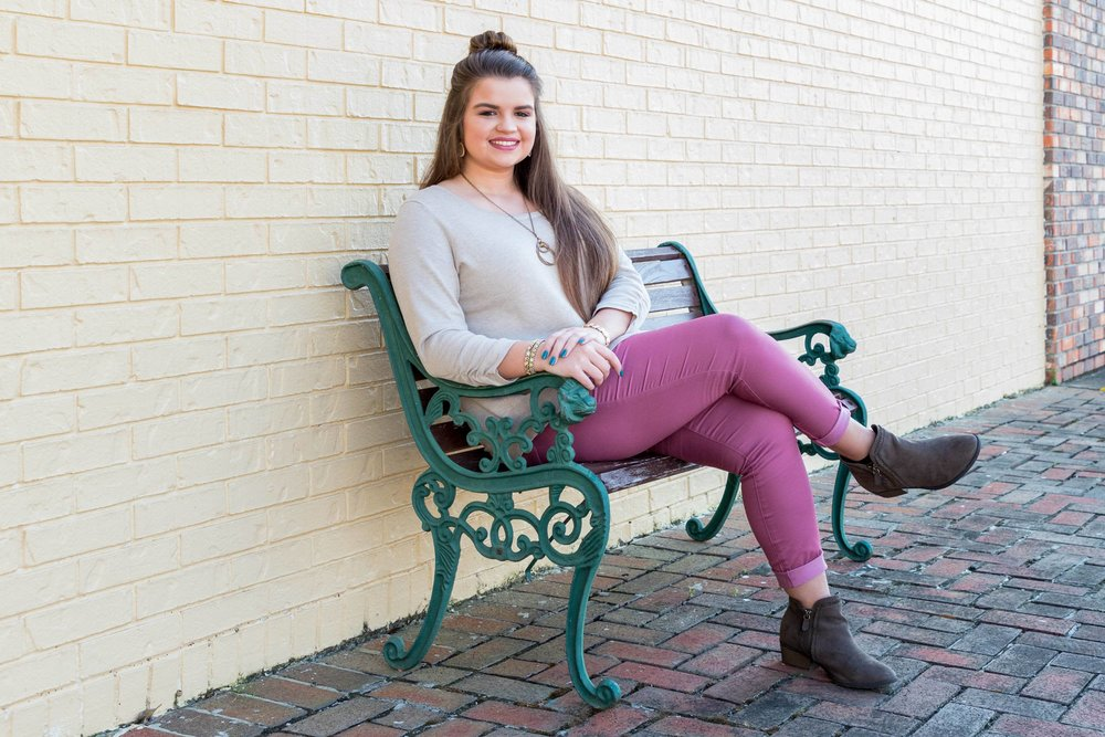 senior girl sitting on bench in downtown Columbia, Mississippi