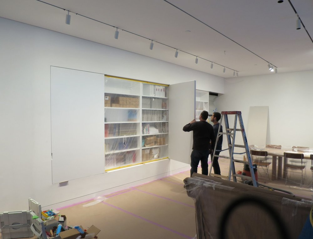 """Pivot doors  – Gallery wall closets, 6 items each 4'10"""" x 6'10"""" with specialty recessed high-end hardware, sheetrock painting and plaster work only at door perimeter, lacquer finish. Construction process photos before doors and hinges are installed."""