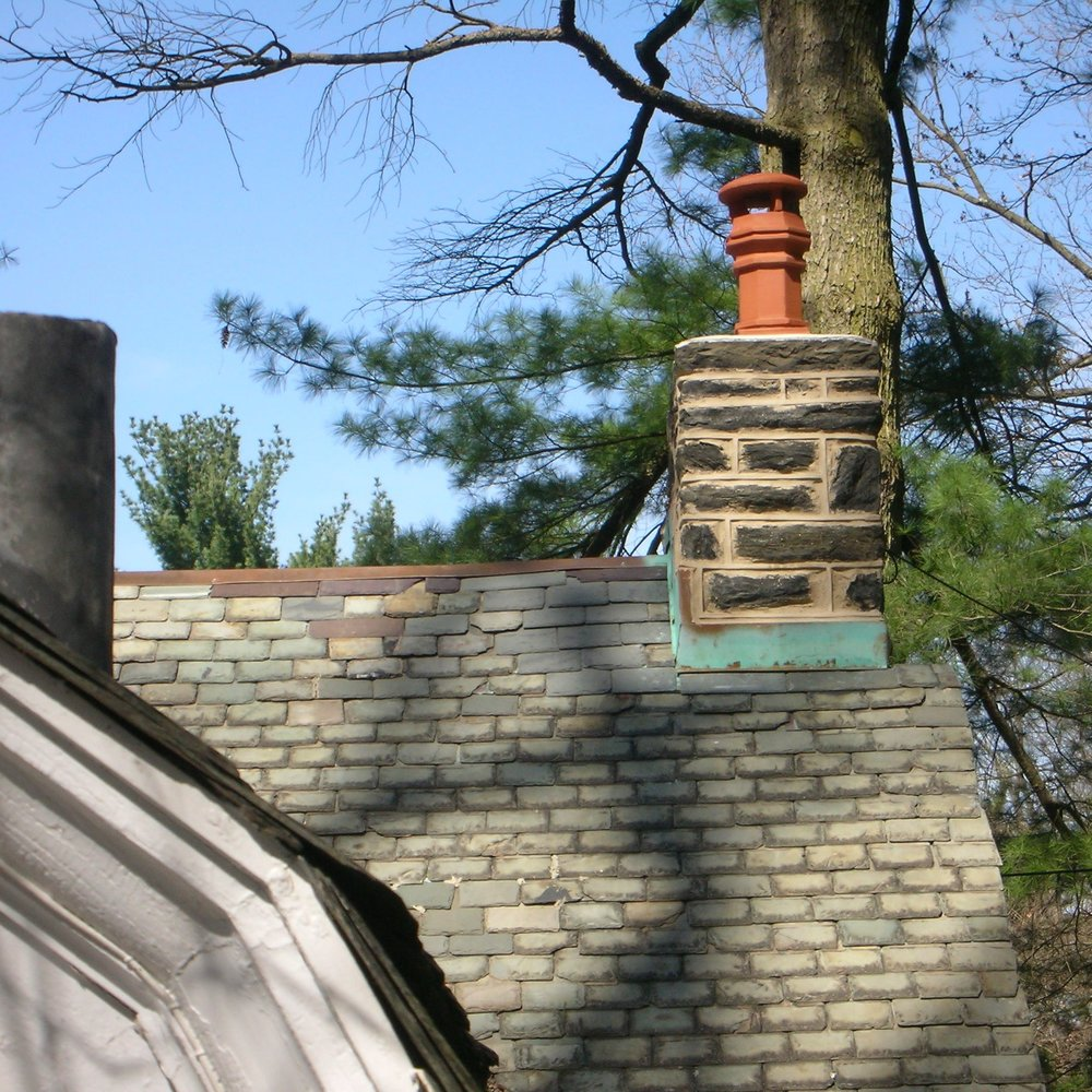 Chimney and flashing following the application of a proprietary solution that accelerates the patina on otherwise new copper flashing, as well as the custom fabrication and later installation of an architecturally compatible ceramic chimney pot.