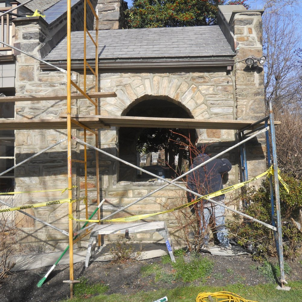 Project site photo of one of our masons applying a lift of natural hydraulic lime mortar to the joints of a traditional arch, in Merion.
