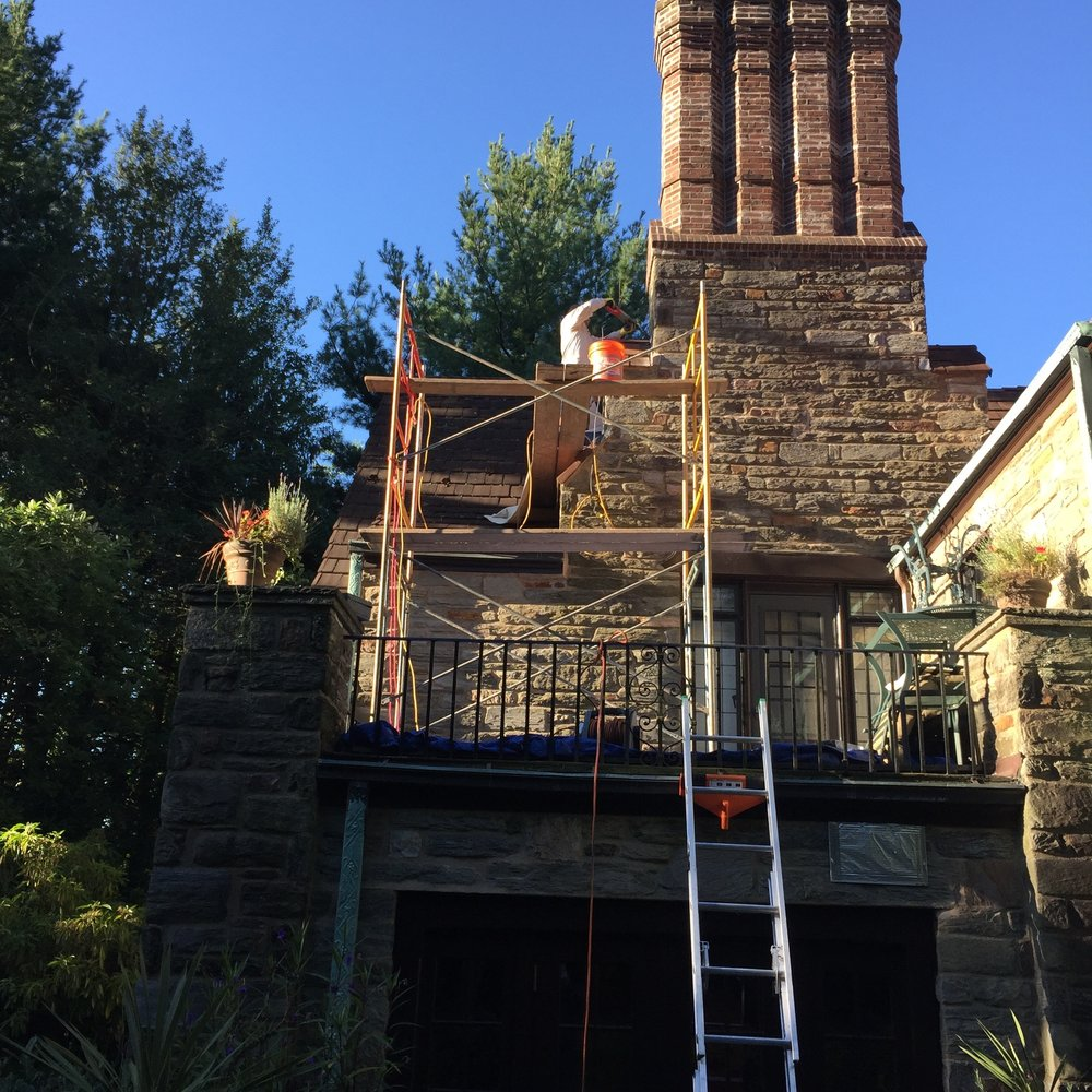 "We love working on ornamental chimneys, both for their beauty and because they are almost always repaired incorrectly. In this case, the chimney was so large and complicated that the previous ""Internet"" contractor neither reglet cut flashing into the masonry nor built a proper cricket (a triangular-prism-looking copper structure that separates the back of the chimney from the roof slope), so water flooded in through the caulked voids. We corrected such errors, as well as replaced any broken or missing Ludowici heritage shingle tiles around the flashing and elsewhere."