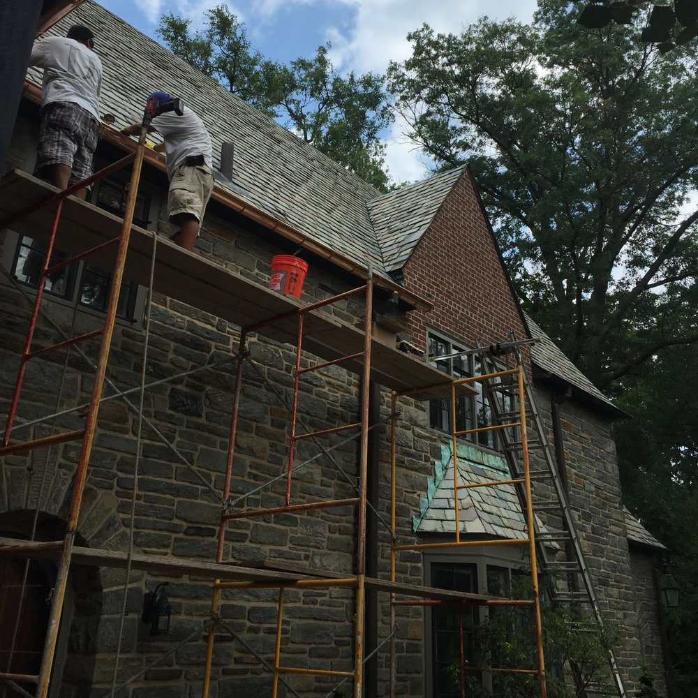 Project site photo of our mechanics repairing the rotted soffit, dislodged gutters, and ice-dam-damaged slate starter course of this historic estate, in Merion. Regarding the gutters, if you look closely enough, we have screwed new gutter hangars into each rafter. That's not something roofers normally do, but if you don't with heavy copper gutters, the additional weight from ice-dams or frozen leaves will tear them right off the woodwork.