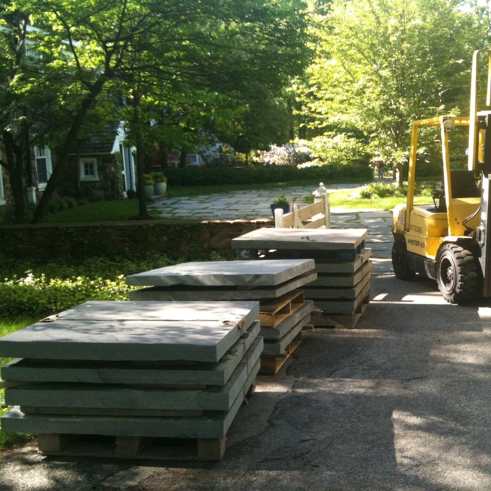 "Project site photo of stacked flagstone replacements – otherwise known as Pennsylvania Bluestone – needed for the partial restoration of a historic driveway that had been severely damaged by constant vehicle traffic, incompatible cement  repairs, salt crystallization, and years of freeze-thaw erosion. Note: given that 6"" or thicker slabs of flagstone were not commercially available at local quarries, we had to visit and then commission a regional quarry operator, in upstate Pennsylvania, to procure suitable replacements – which we later cut to dimension, on-site."