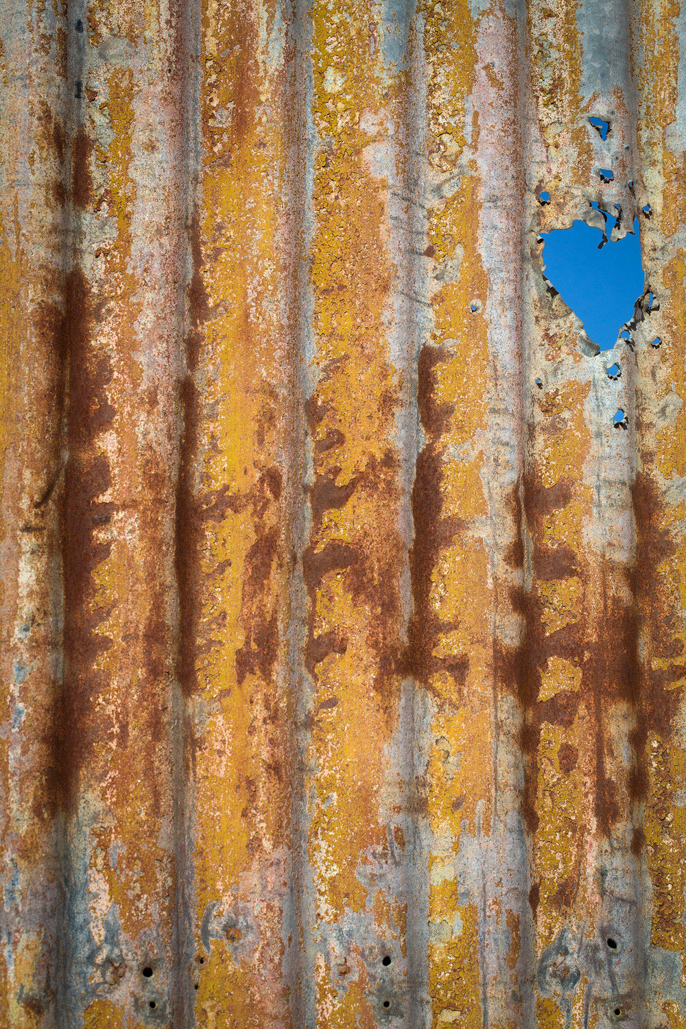 A patch of blue sky peeks through a corrugated iron fence at a closed mine, Broken Hill, NSW.