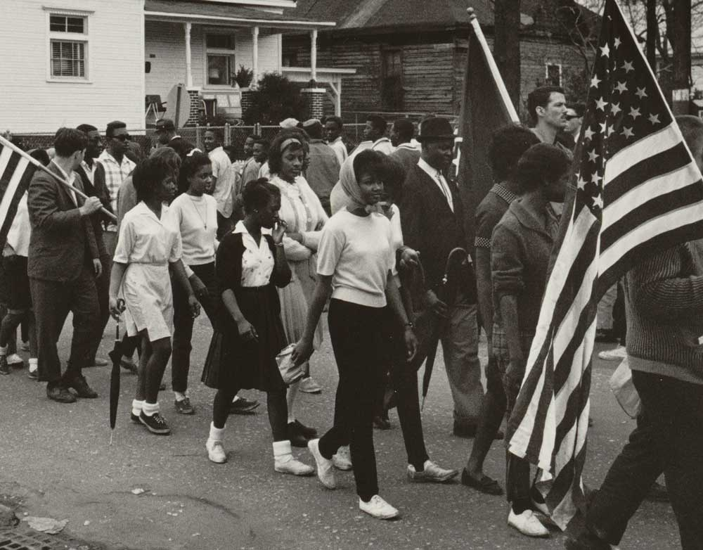 Participants, some carrying American flags, marching in the civil rights march from Selma to Montgomery, Alabama in 1965. Photo by Peter Pettus
