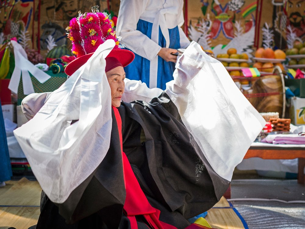 "Manshin Kim Keum-Hwa performs at her shrine in Ganghwa Island, South Korea. Kim Keum-Hwa is a famous shaman, designated by the South Korean government as an ""Intangible Cultural Treasure."" This three-day ritual was held to celebrate her 70th anniversary as a shaman."