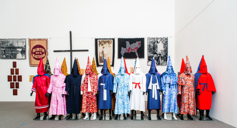 """There have been more than 4,300 documented lynchings in the US, mostly of African-American people. I created a series of cotton woven throws [shown on wall] and each depicts the image of a lynching or killing,"" says Rucker. ""They capture experiences of extreme human atrocity in objects that were designed for comfort, warmth and security."""