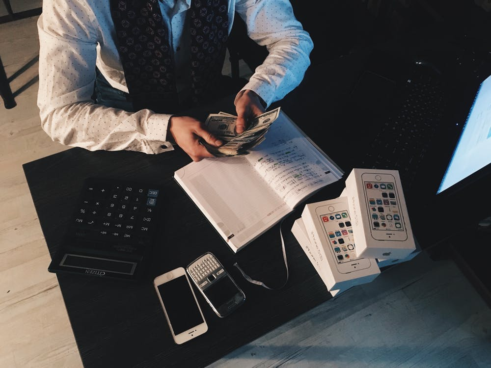 Man holding cash with a calculator and accounting notebook on table