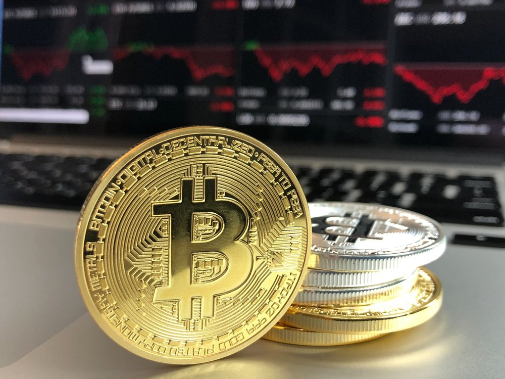bitcoins stacked on a desk with computer in the background